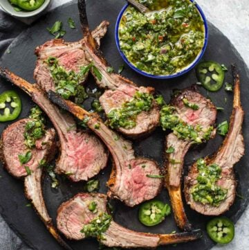 Grilled Lamb lollipops with Jalapeño chimichurri on a serving platter.