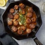 Grilled Scallops in a white wine pan sauce in cast iron pan.