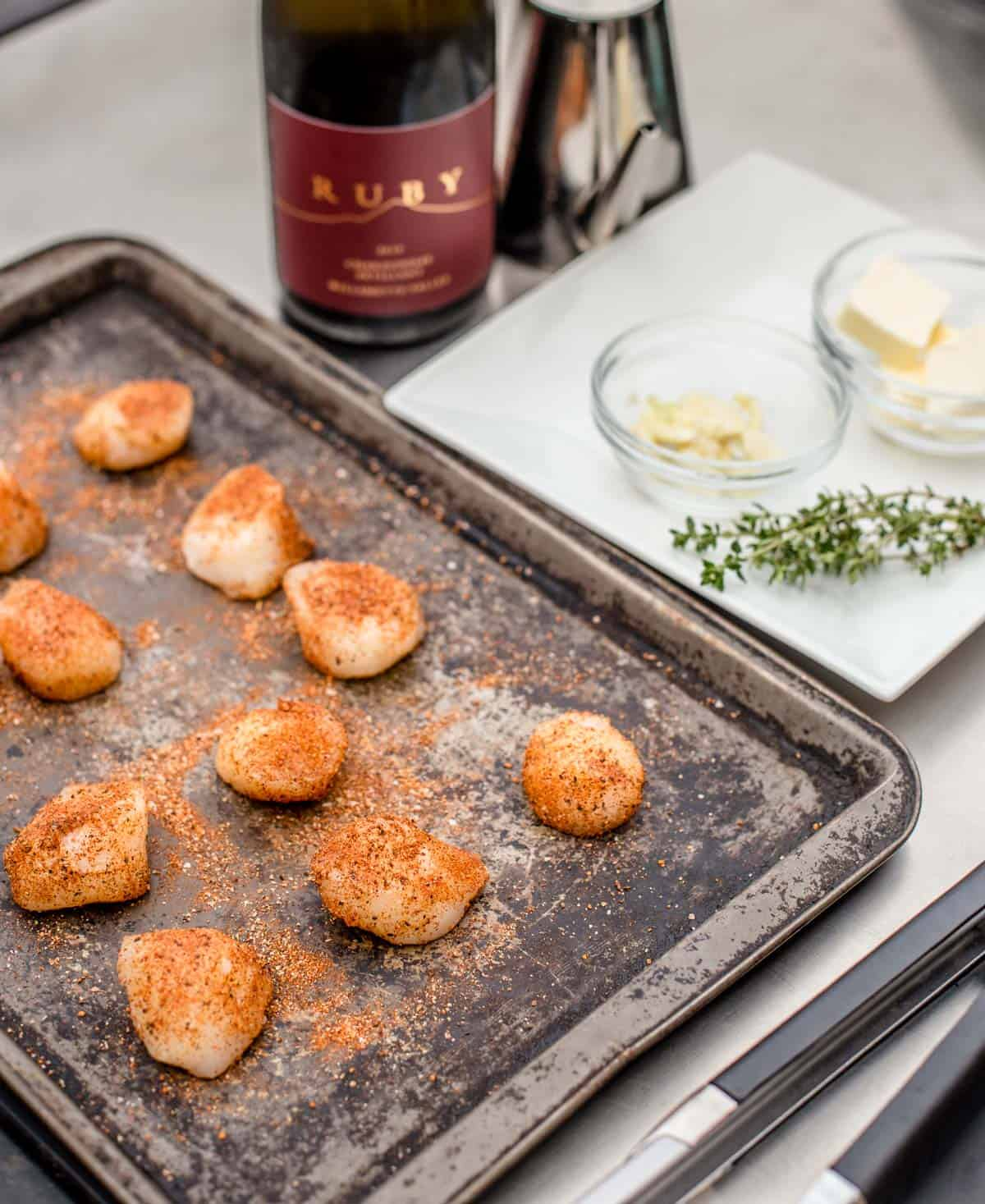scallops on a sheet pan with seafood seasoning on them