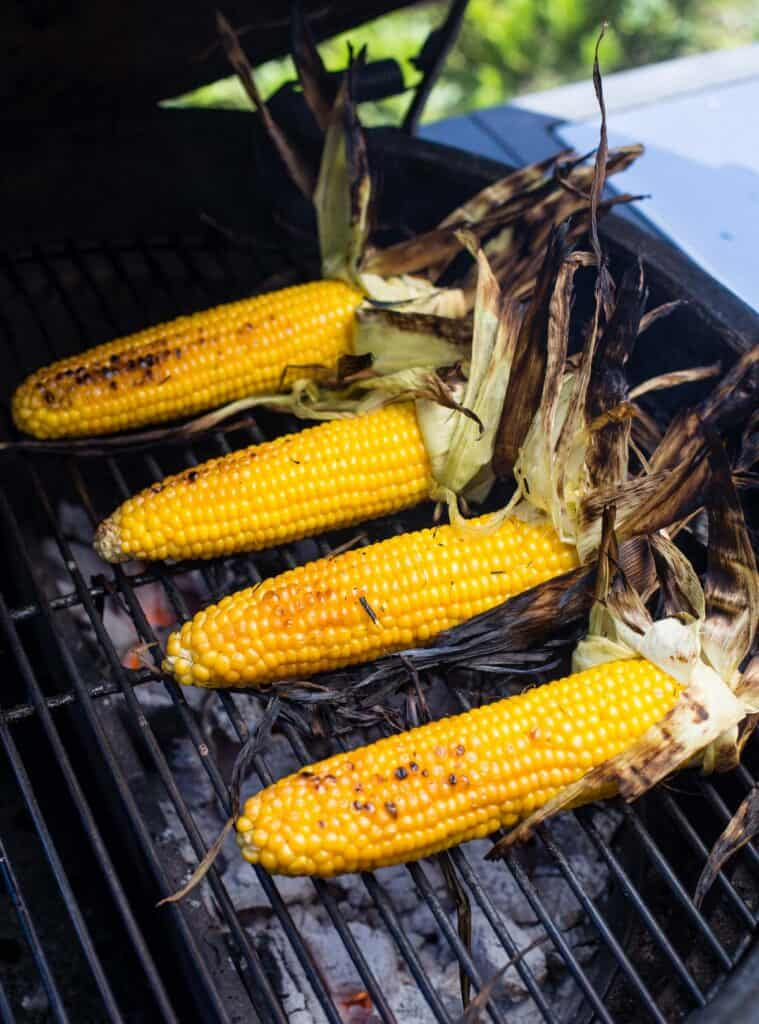 Grilled Corn with husks removed on a grill.