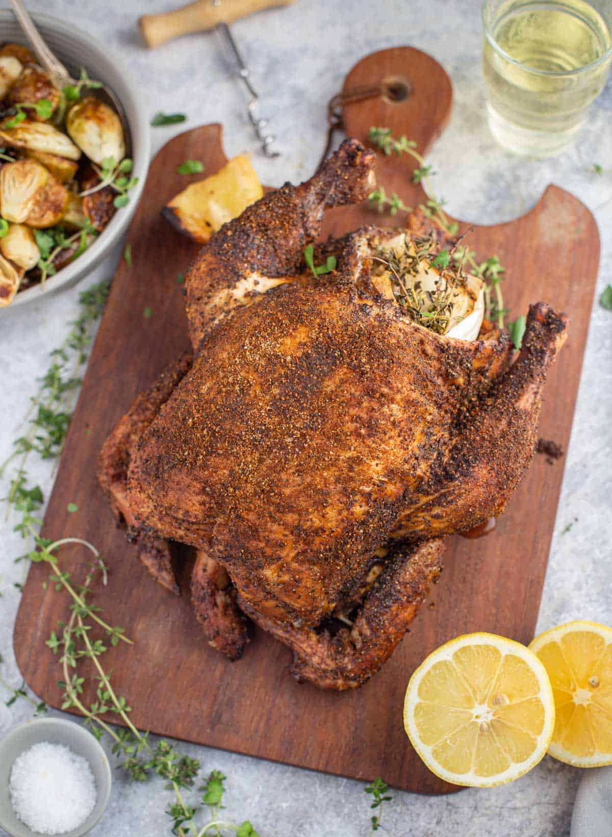 A whole chicken grilled in a pellet smoker on a cutting board