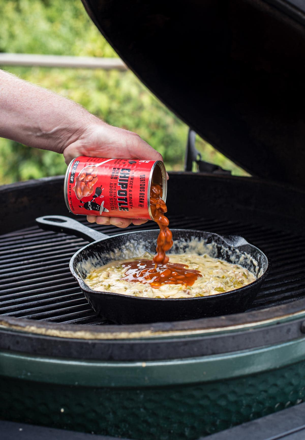 Pouring a can of beans into a queso dip on a grill