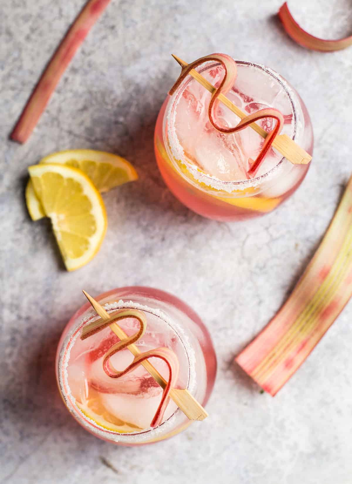 Top down view of two cocktails with rhubarb simple syrup and lemon