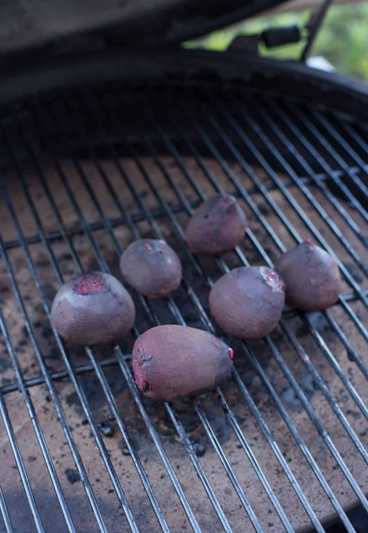 6 red beets smoking on a grill