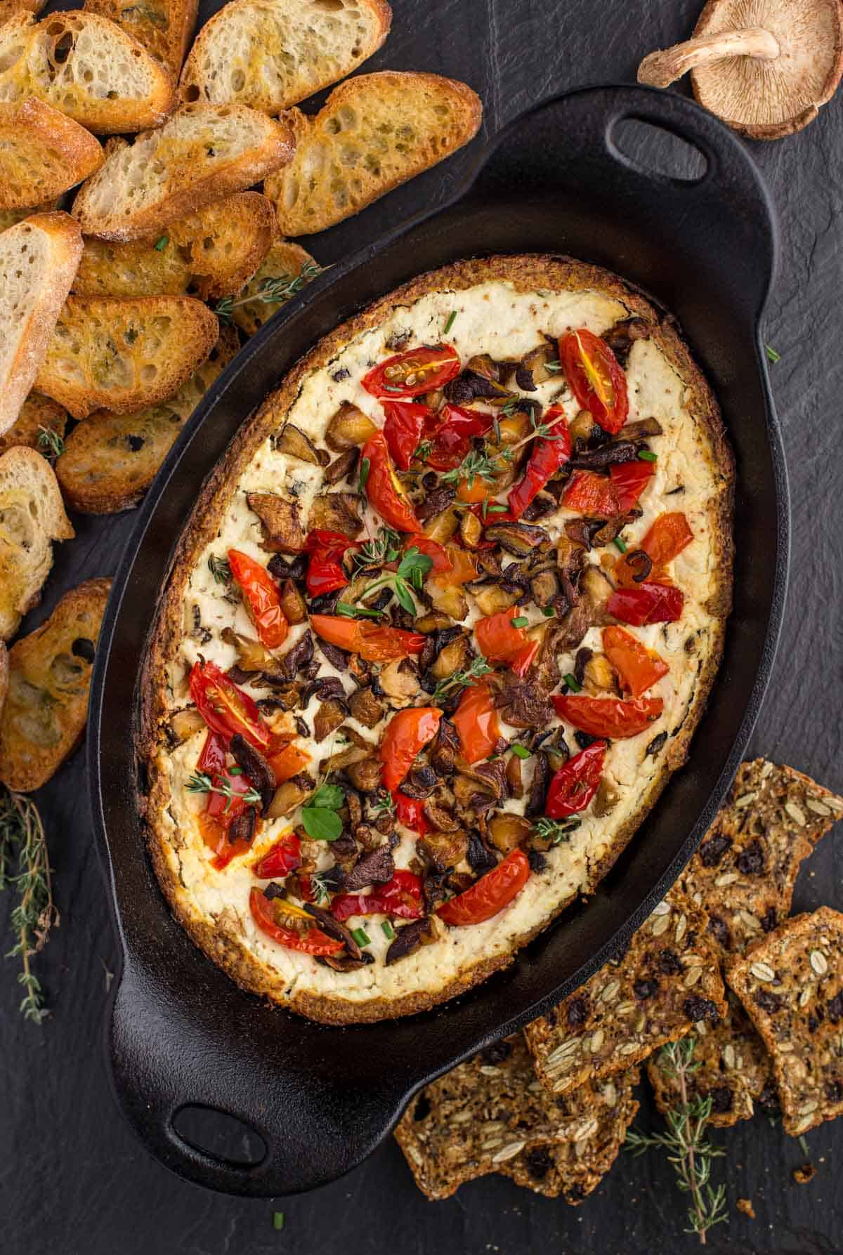 Goat Cheese Dip With Shitake Mushrooms, pickled peppers, and tomatoes in a serving platter with some baguette on the side