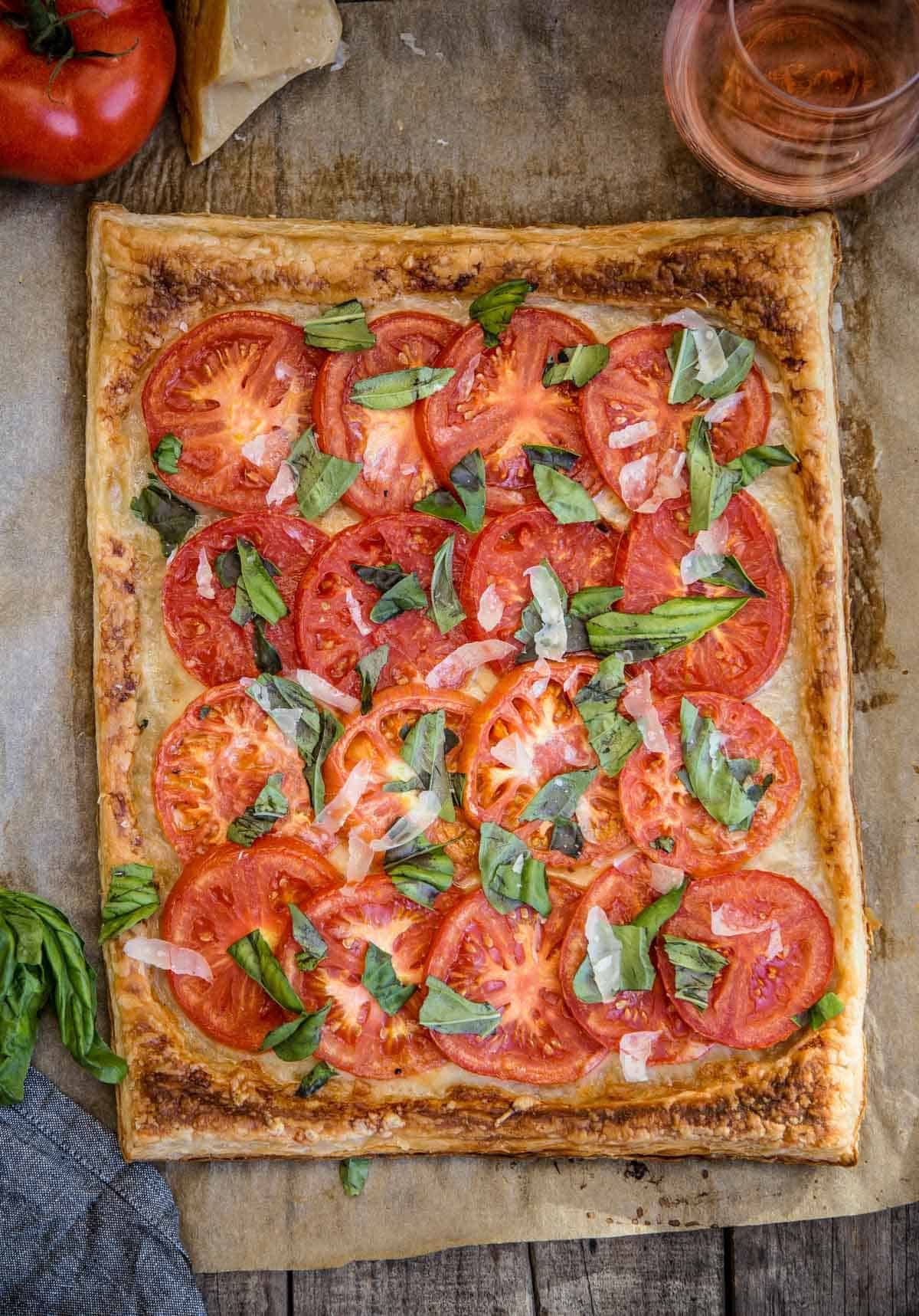 A fresh summer tomato galette on a serving platter with a glass of wine