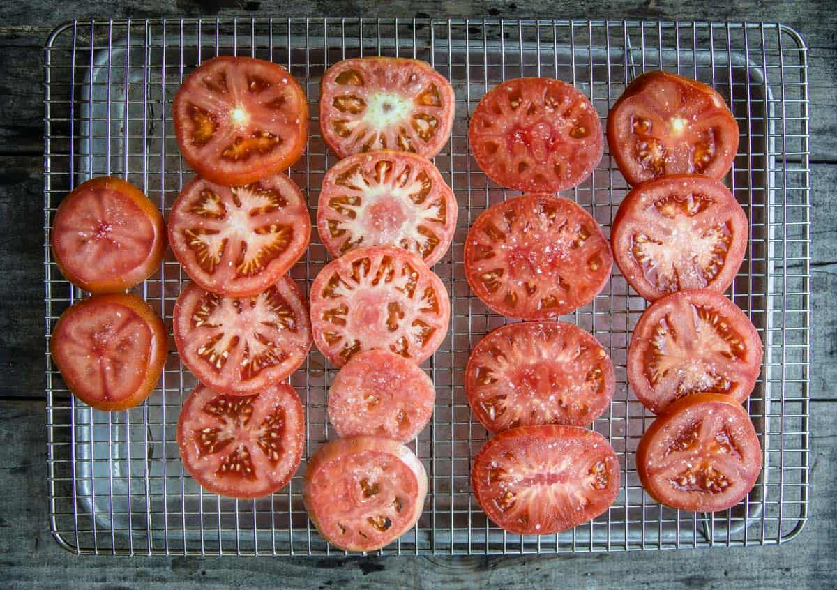 Fresh slices of summer tomatoes on a drying rack