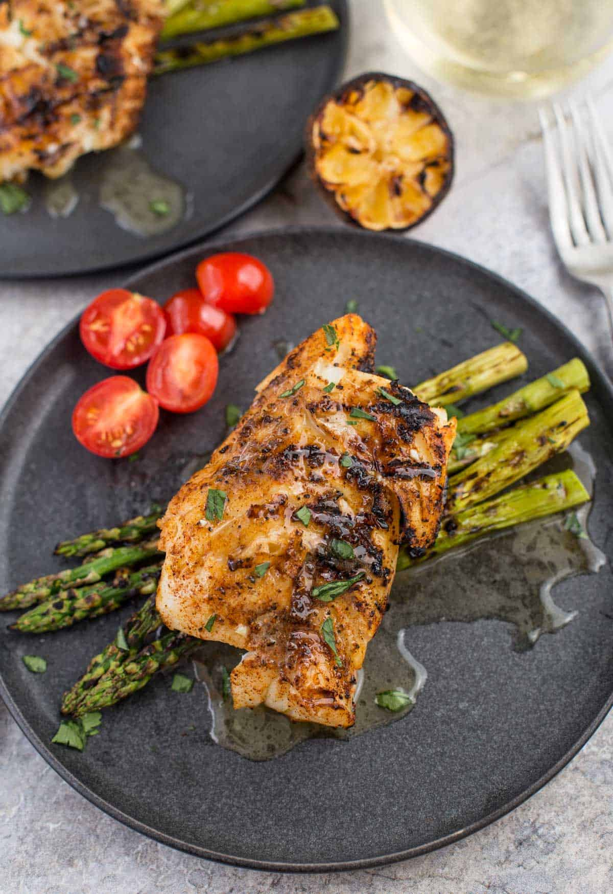 Grilled Cod with White Wine Butter Sauce on a plate with grilled asparagus and cherry tomatoes