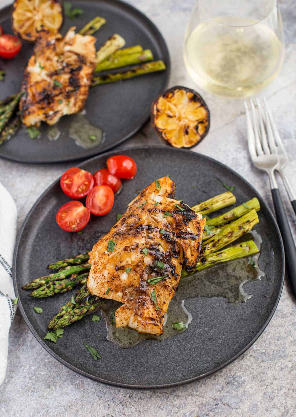 Grilled cod with white wine butter sauce on a platter with grilled asparagus
