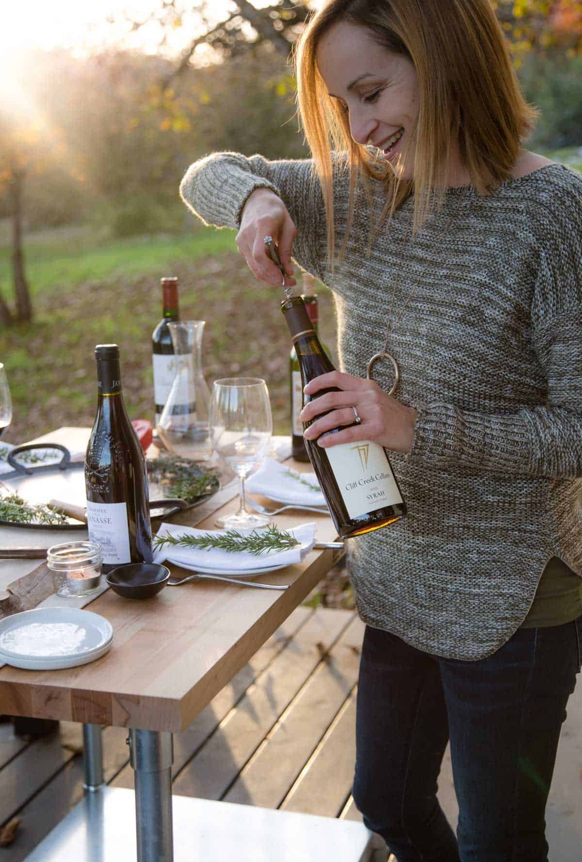 Woman opening a bottle of Syrah Wine