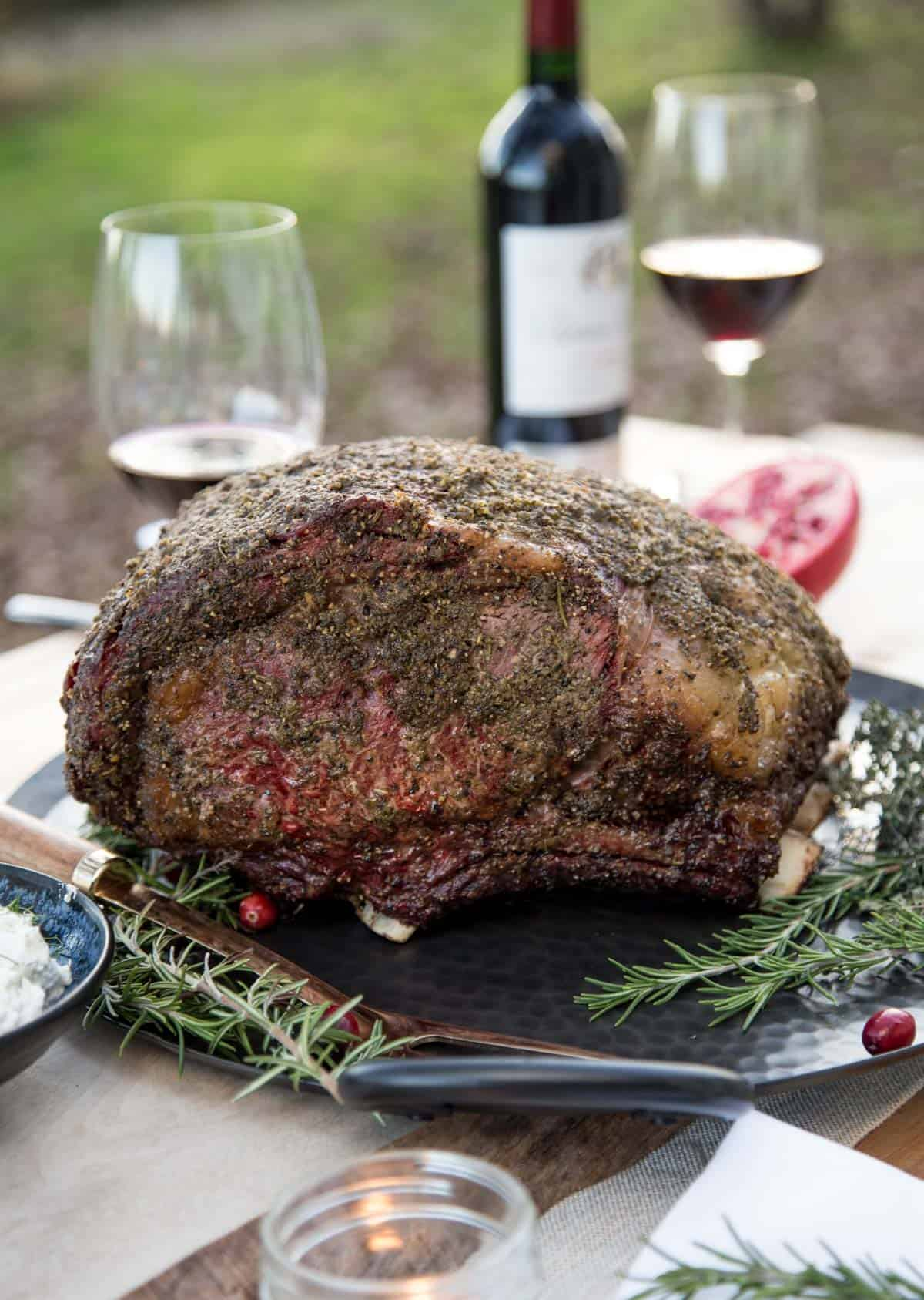 A smoked prime rib on a platter with a bottle of Syrah wine in the background