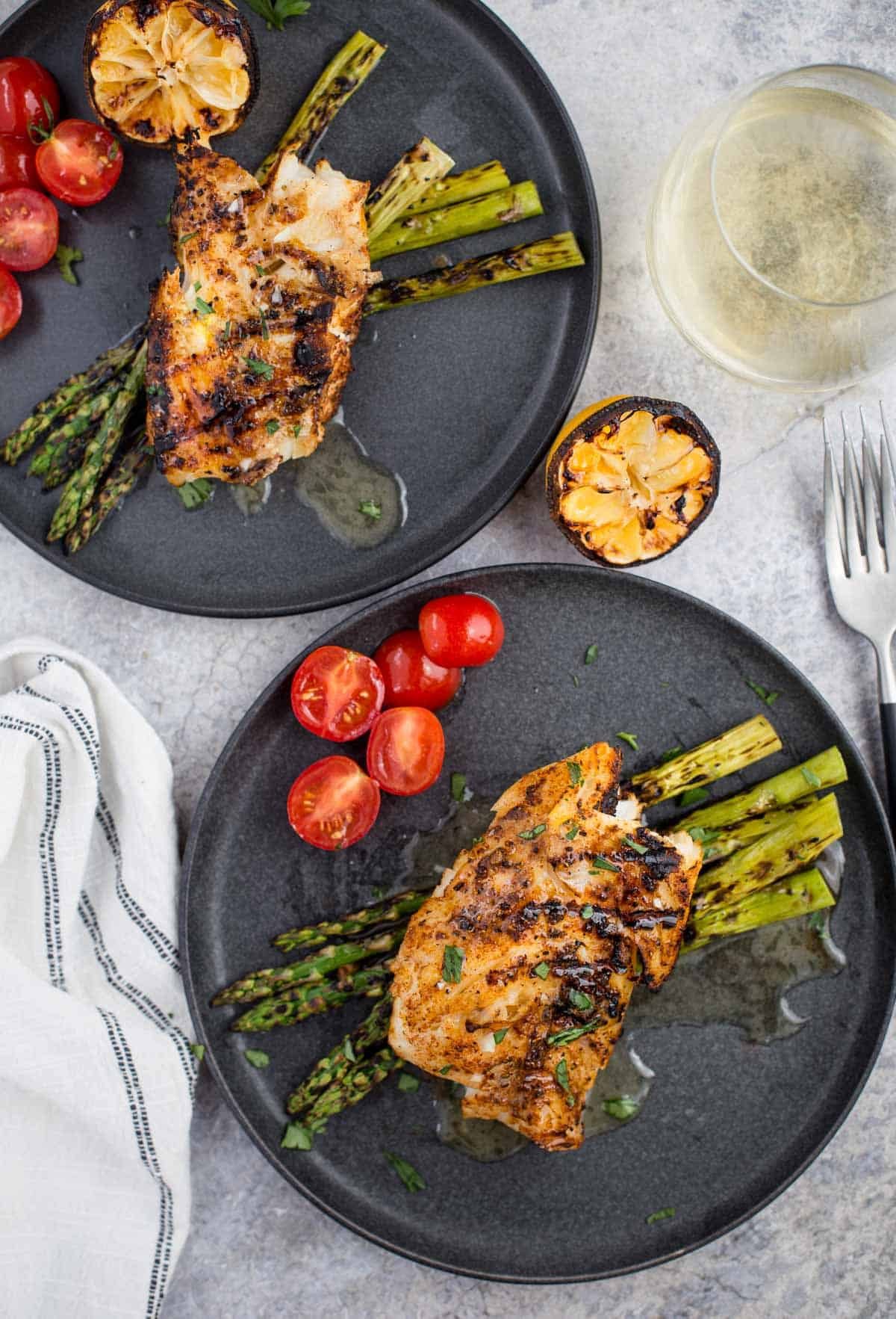 Two plates with grilled cod and a glass of white wine