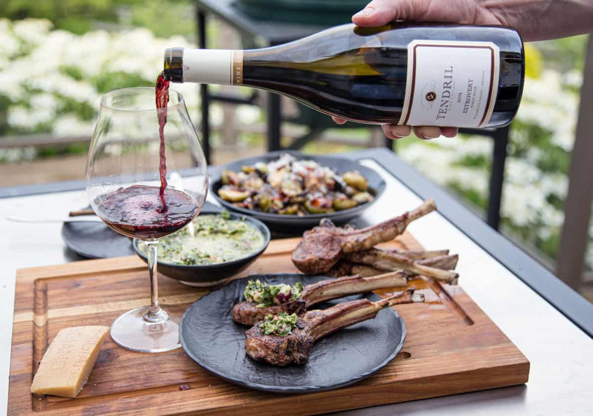 A glass of red wine being poured next to a plate of grilled lamb chops for a great wine and food pairing