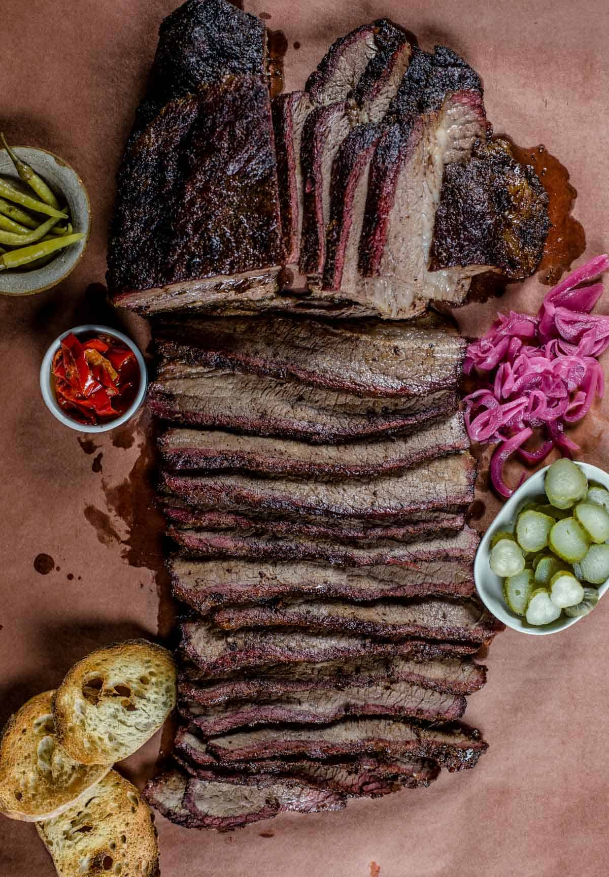 Smoked brisket sliced on pink butcher paper with garnishes