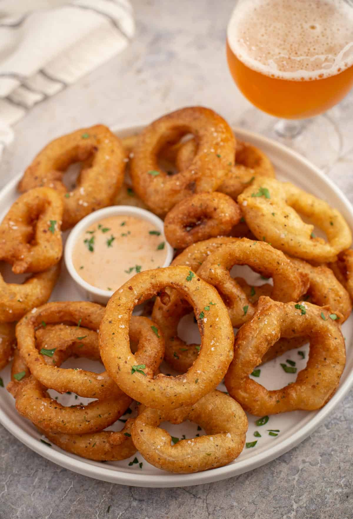 A platter of smoked onion rings and a glass of beer