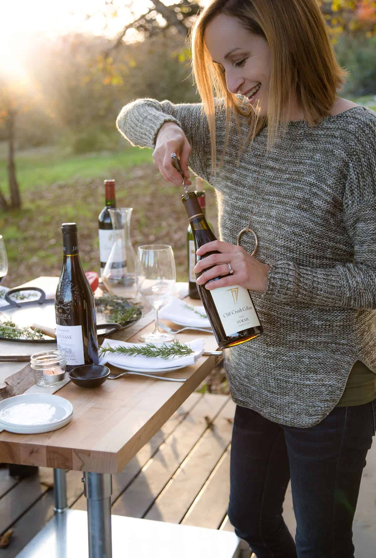 Mary Cressler, sommelier, opening up  a bottle of wine for a Thanksgiving dinner spread