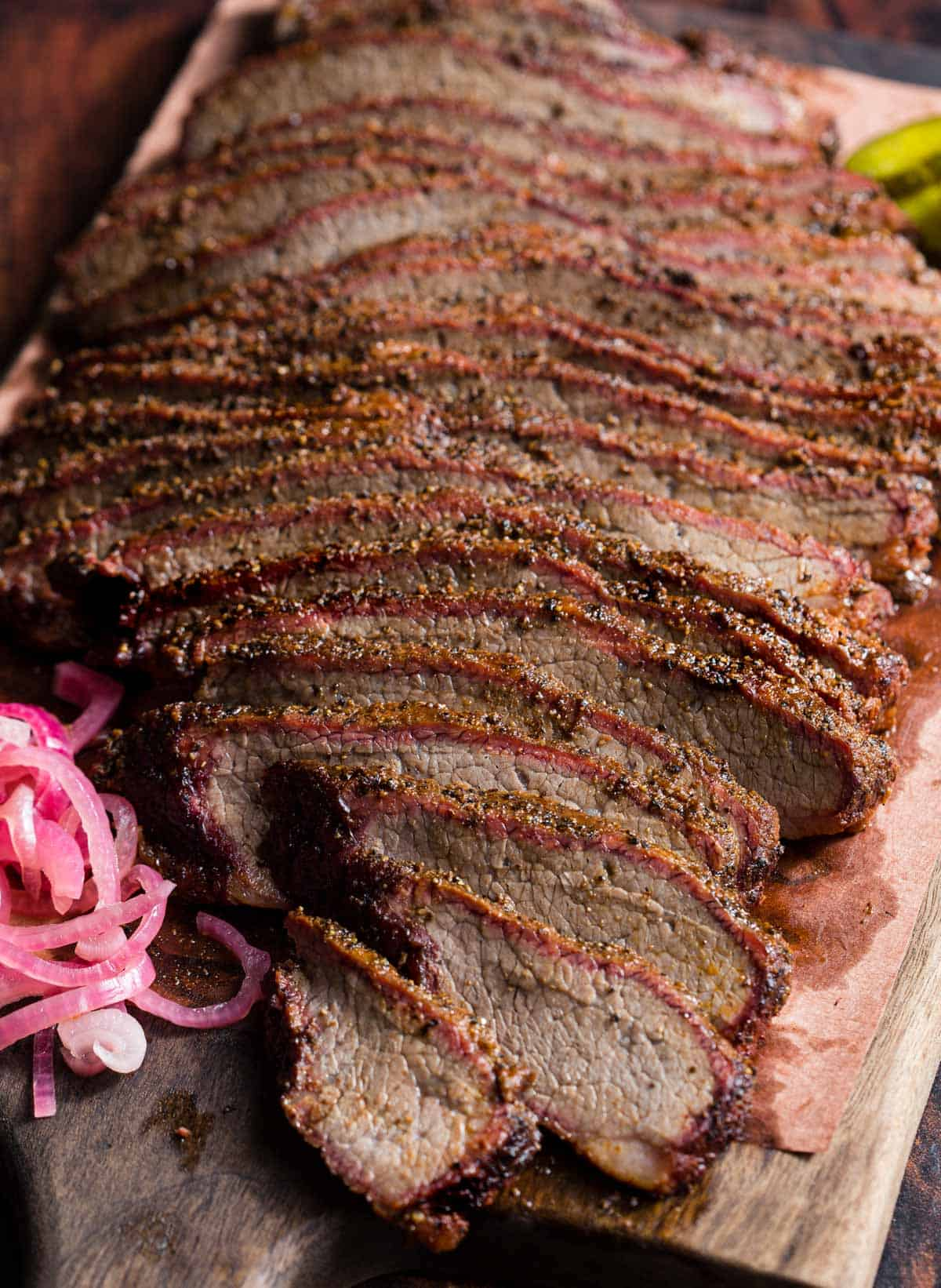 Slices of smoked brisket flat on a platter with garnishes