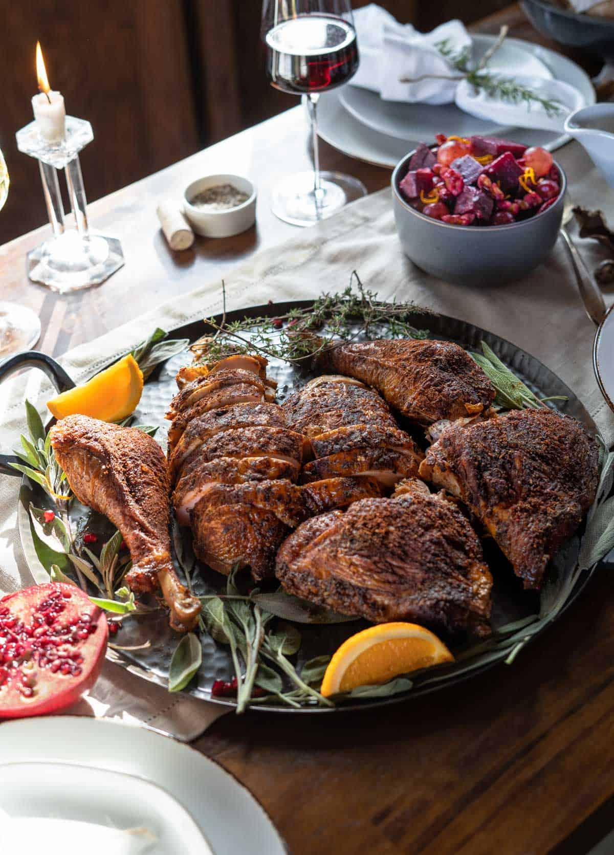 A Smoked Turkey on a table with other Thanksgiving side dishes in a lovely holiday tablescape